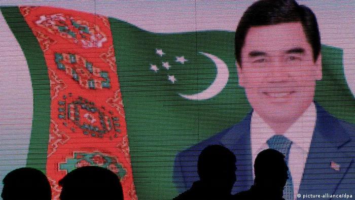 Силуэты людей на фоне портрета президента Туркмении