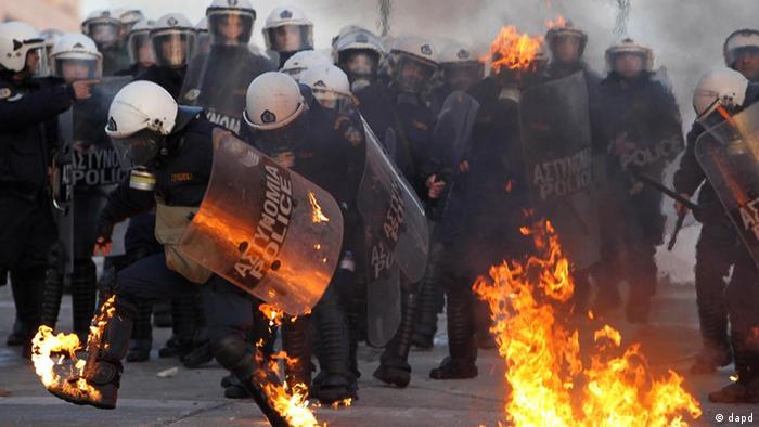 A riot police officers tries to extinguish flames from a petrol bomb thrown by protestors outside the Greek parliament, Athens, Sunday, Feb. 12, 2012. Tens of thousands of protesters gathered in the square outside Parliament as a parliamentary debate began, with more arriving constantly. As the crowds grew, a few hundred anarchists started to throw bottles and firebombs at police, who responded with tear gas and stun grenades. (Foto:Thanassis Stavrakis/AP/dapd)