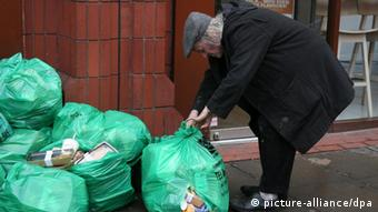 A picture from London showing a poor man picking left over sandwiches from the rubbish bags at the end of the day outside a sandwich shop(Photo: Jon Almasi/UPPA )