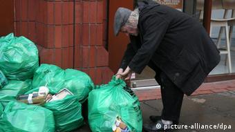Older person picking through trash bags outside a food shop Copyright: Jon Almasi/dpa