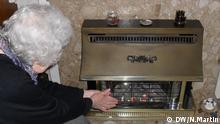 Ältere Frau wärmt sich die Hände am Kaminofen