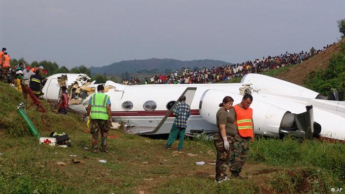 In this photo taken on Sunday, Feb 12, 2012, rescue workers investigate the site of an airplane crash in Bukavu, Congo. A senior presidential adviser was among two killed after the private jet crashed while landing in Congo's eastern city of Bukavu, a transport minister said Sunday. We've extracted two bodies from the plane, that of the honorable Augustin Katumba Mwanke who has just been moved to the morgue, and that of a co-pilot, said Provincial Transport Minister Laban Kyalangalilwa. He said there were 2 pilots and 10 passengers on the private jet.(AP Photo)