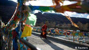 A Tibetan Buddhist nun from the Ganden Jangchup Choeling nunnery crosses a bridge near the town of Daofu, Sichuan province, in this November 13, 2011 file photo. An 18-year-old Tibetan nun died after setting herself on fire in protest at Chinese rule in Tibet, activists said on February 12, 2012, adding to a fast growing list of self-immolations in ethnically Tibetan areas of China. Chinese army troops moved in after Tenzin Choedon set herself alight at the Mamae convent in China's southwestern Sichuan province, said Kanyag Tsering, a monk in Dharamsala, India, where the Tibetan government-in-exile is based. REUTERS/Carlos Barria/Files (CHINA - Tags: POLITICS CIVIL UNREST RELIGION)