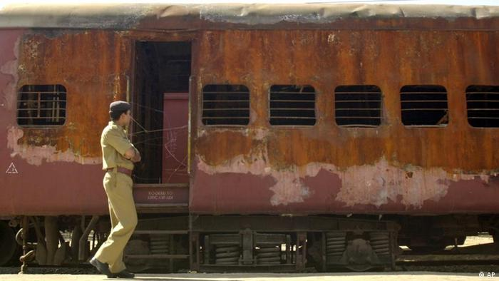 An unidentified policeman walks past the burnt S-6 coach of Sabarmati Express train at Godhra, India, Tuesday Feb. 25, 2003. Mosques, Hindu temples, train and bus stations in the western state of Gujarat will come under heavy police guard on Thursday, Feb. 27, 2003, the anniversary of a train attack that triggered India's worse religious violence in a decade. (AP Photo/Siddharth Darshan Kumar)