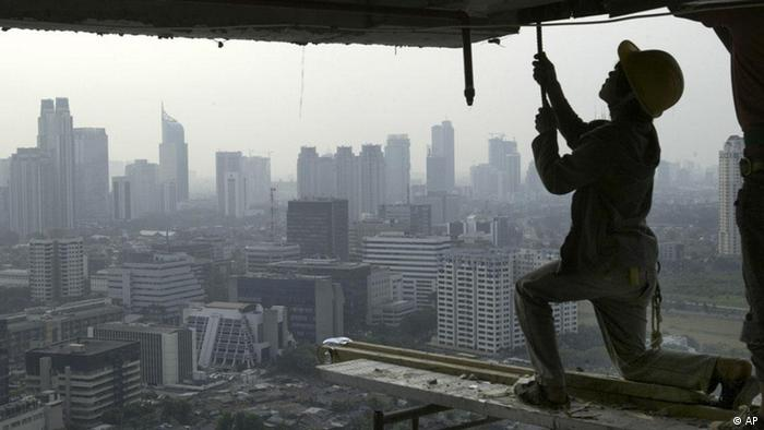 An Indonesian construction worker adjusts a fitting on the 50th floor of a new building Tuesday July 1, 2008, in Jakarta, Indonesia. Asia's growth is threatened by spiraling inflation from higher food and fuel costs, an Asian Development Bank executive warned Sunday, and called on governments to tighten monetary policies to deal with the scourge.(ddp images/AP Photo/Tatan Syuflana)
