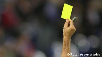 A soccer referee holding up a yellow card