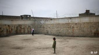 An inmate walks with her infant child as a child of another inmate stands nearby in the prison yard at Pul-e Charkhi prison in Kabul, Afghanistan April 17, 2008. There are 226 young children in Afghanistan's prisons, including many who were born there. They have committed no crime, but they live among the country's 304 incarcerated women. (ddp images/AP Photo/David Guttenfelder)