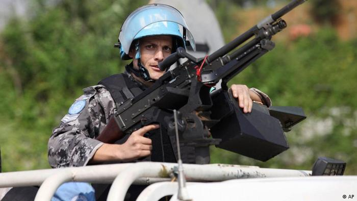 A UN peacekeeper in a blue helment behind a machine gun on patrol Photo: ddp images/AP Photo/Sunday