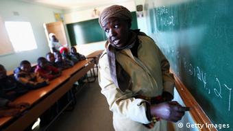 A teacher standing near a blackboard. (Photo by Brent Stirton/Getty Images)