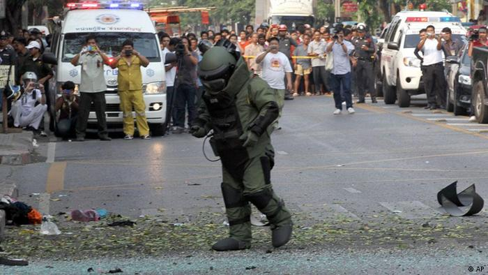 A Thai Explosive Ordnance Disposal (EOD) official examines the bomb site in Bangkok, Thailand Tuesday, Feb. 14, 2012. Two explosions boomed through a busy neighborhood in the Thai capital Tuesday, police said, but it was not immediately clear what caused the blasts or whether there were any fatalities. (Foto:Apichart Weerawong/AP/dapd)