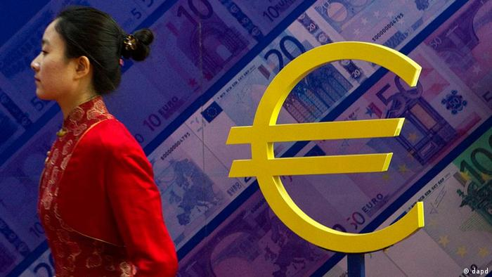 A Chinese woman walks past a euro sign