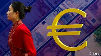 A hostess walks past the euro sign at an exhibition about currencies in Beijing