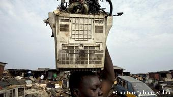 A boy carries the shell of a computer monitor