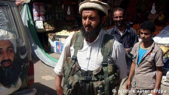 Al-Qaeda-linked fighters in the Yemeni town of Rada An al-Qaeda-linked fighter stands next to a poster of the late head of al-Qaeda Osama bin Laden, while patrolling at a street in the southeast town of Rada, Yemen, 21 January 2012. According to media sources, Yemeni tribal forces in the town of Rada have prevented al-Qaeda-linked fighters from pressing into the town. The al-Qaeda fighters, who seized the town of Rada a week ago, demanded the release of 15 militants from Yemeni prisons before they could withdraw. EPA/STR +++(c) dpa - Bildfunk+++