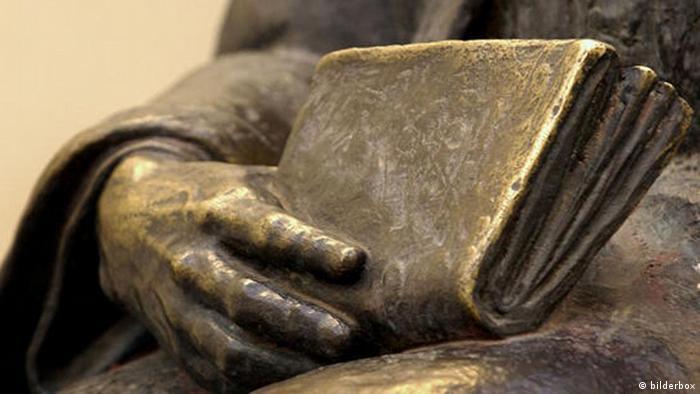 Статуя на човек с книга в ръка