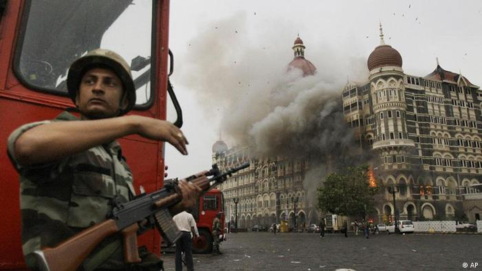 In this Nov. 29, 2008 file photo, an Indian soldier takes cover as the Taj Mahal hotel burns during gun battle between Indian military and militants inside the hotel in Mumbai, India.(Photo: AP)