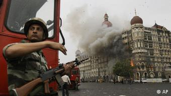 An Indian soldier takes cover as the Taj Mahal hotel burns during gun battle between Indian military and militants inside the hotel in Mumbai, India (Photo: David Guttenfelder, File/AP/dapd)