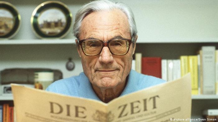 Homem velho de óculos lendo jornal