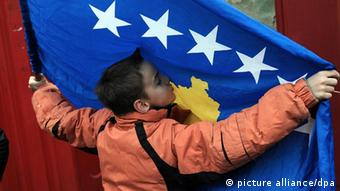 A child kisses Kosovo's flag