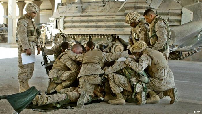 U.S. Marines pray over a fallen comrade at a first aid point after he died from wounds suffered in fighting in Fallujah, Iraq, Thursday, April 8, 2004. Hundreds of U.S. Marines have been fighting insurgents in several neighborhoods in the western Iraqi city of Fallujah in order to regain control of the city. This photograph is one in a portfolio of twenty taken by eleven different Associated Press photographers throughout 2004 in Iraq. The Associated Press won a Pulitzer prize in breaking news photography for the series of pictures of bloody combat in Iraq. The award was the AP's 48th Pulitzer. (AP Photo/Murad Sezer)