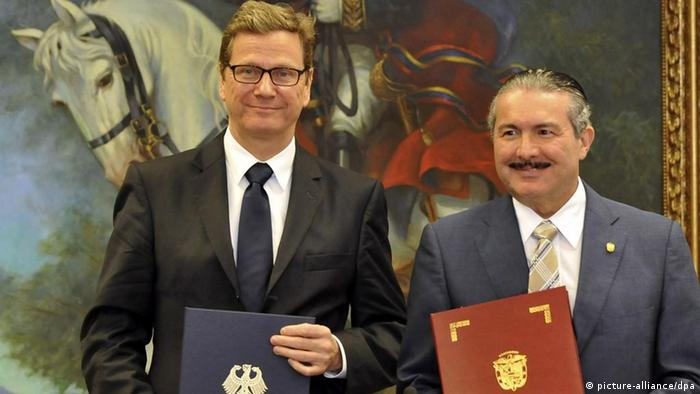 epa03110885 German Foreign Minister Guido Westerwelle (L) and his Panamanian counterpart Roberto Henriquez (R), pose for a photo after the signing of a diplomatic agreement in Panama City, Panama, 17 February 2012. EPA/ALEJANDRO BOLIVAR