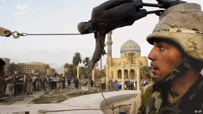 Iraqi civilians and U.S. soldiers pull down a statue of Saddam Hussein in downtown Baghdad Wednesday April 9, 2003. (AP Photo/Jerome Delay)
