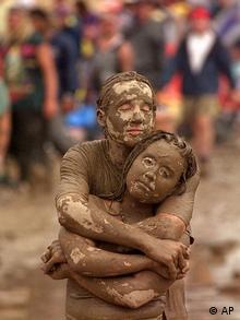 Zwei schlammverschmierte Menschen umarmen sich. AP Iconic Images USA Woodstock '94