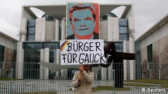 A demonstrator holds a sign supporting German politician Joachim Gauck as president