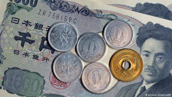 Japanese yen coins lying on a 1,000-yen banknote