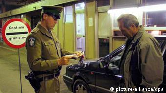 A polish immigration officer checks the documents of a Ukrianian citizen