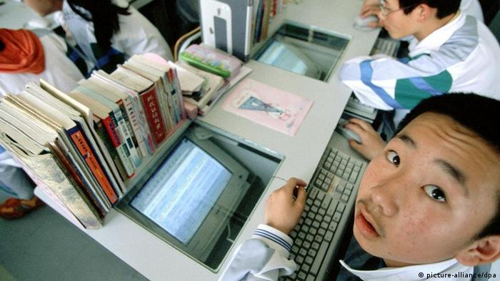 Young Chinese students sit hunched over computers