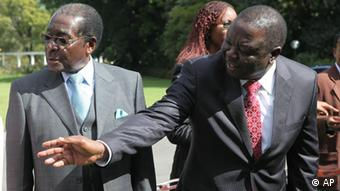 Zimbabwe President Robert Mugabe, left, talks to Morgan Tsvangirai, Zimbabwe Prime Minster after the swearing in ceremony of new ministers at State House in Harare, Thursday, June, 24, 2010.