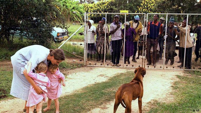 In this file photo dated March 29, 2000, Pippa van Rechteren, left, and her two-year-old twins Catherine, second from left, and Elisabeth, third from left, are blocked from leaving their house on the white-owned commercial farm, Chiripiro, by Zimbabwe war veterans in Centenary district, 150 kilometers (93 miles) north of Harare.