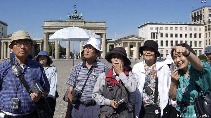 Eine chinesische Touristengruppe geht bei schönem Sommerwetter über den Pariser Platz vor dem Brandenburger Tor in Berlin.