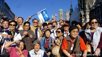 ARCHIV - Eine Reisegruppe aus China besichtigt den Münchner Marienplatz (Archivfoto vom 02.09.2004). Als erster europäischer Reiseveranstalter steigt TUI ins rasant wachsende Geschäft mit Auslandsreisen von Chinesen ein. Das Potenzial ist enorm: Bis 2020 soll sich die Zahl der chinesischen Touristen in Europa auf voraussichtlich acht Millionen vervierfachen. Foto: Frank Mächler dpa +++(c) dpa - Bildfunk+++