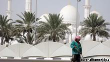 ARCHIV - Ein ausländischer Arbeiter fegt die Straße vor der Scheich-Said-Moschee in Abu Dhabi (Archivfoto vom 28.06.2009). Mehr als zehn Millionen ausländische Arbeiter schuften derzeit in den arabischen Golfstaaten. Ohne diese mehr oder weniger rechtlosen Niedriglohnarbeiter aus Asien, die oft mehr als zwölf Stunden pro Tag arbeiten, wäre das Wirtschaftswachstum nicht denkbar. Foto: Anne Beatrice Clasmann dpa (zu dpa-Korr.: Hitzige Debatte um moderne Sklaverei am Golf vom 11.06.2009) +++(c) dpa - Report+++ Schlagworte Straßenszene, Palmen, kuppel, Kopfbedeckung, Straßenfeger, Gestik, halten, Turm, Kopftuch, sklavLÆ, Politik, Arbeit, Gebäude