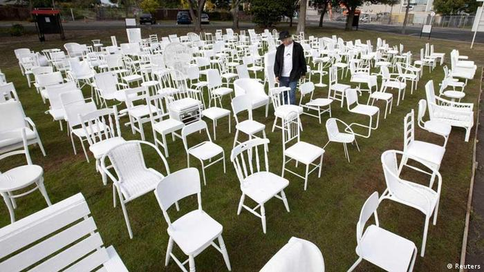 Artist Pete Majendie walks among his temporary art installation of 185 white painted chairs which represent the 185 lives lost in the 2011 Christchurch earthquake