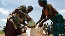 An unidentified woman receives grains at the CARE food distribution centre in Douloukou, Niger Monday, Aug. 8,2005. Hunger, a perennial problem in Niger, Mali, Mauritania and Burkina Faso, was compounded by a locust invasion last year followed by drought. The U.N. says millions now face severe food shortages. (AP Photo/George Osodi)