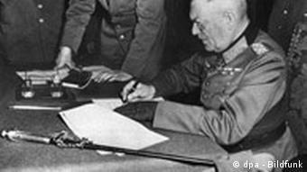 Feldmarschall Wilhelm Keitel, Oberkommandierender der Wehrmacht (1938-45), unterschreibt in Berlin-Karlshorst die Kapitulations-Urkunde der deutschen Wehrmacht (Archivbild vom 08.05.1945). Der Zweite Weltkrieg ging in der Nacht vom 08. zum 09. Mai 1945 zu Ende, nachdem Generaloberst Alfred Jodl im französischen Reims die Kapitulation unterzeichnet hatte. Der Akt wurde in Berlin von Feldmarschall Keitel mit den sowjetischen Vertretern wiederholt. Zum 55. Jahrestag des Kriegsendes erinnern 2000 Ausstellungen und Gedenkfeiern in Berlin an die Zeit des Holocaust. dpa (zu dpa-Bericht Gedenken an den Holocaust: Vor 55 Jahren endete der Zweite Weltkrieg am 05.05.2000) nur s/w