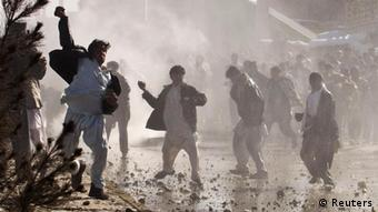 Afghan protesters throw rocks towards a water canon near a US military base in Kabul
