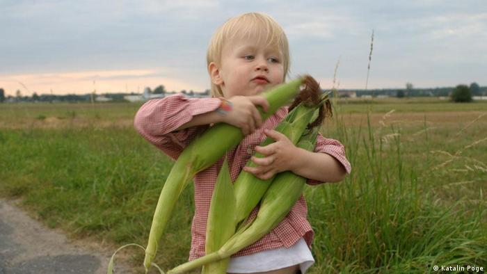 Kind trägt Maiskolben