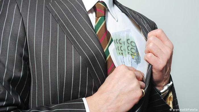 A man putting money into an inside pocket of his suit jacket Fotolia.com © granata68 #28961612