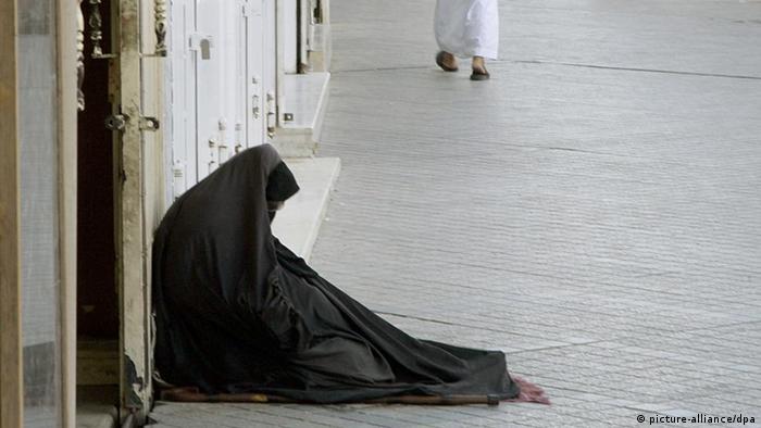 Eine schwarz gekleidete Bettlerin mit einem Krückstock neben sich, kauert am Rande einer Straße in Riad, der Hauptstadt des Königreiches Saudi-Arabien, aufgenommen am 15.11.2006. Foto: Peer Grimm + + + (c) dpa - Report + + +