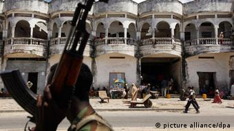 A Somali government soldier walks in front of a destroyed hotel (Photo: Dai Kurokawa)