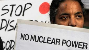 A woman living near Kudankulam atomic plant holds a placard as she participates in an anti-nuclear protest