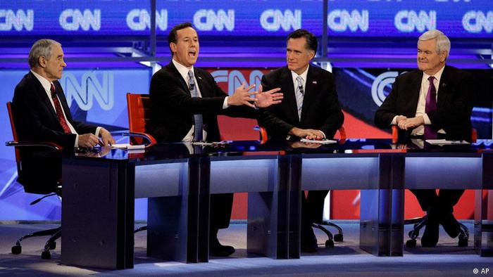 Republican presidential candidates Rep. Ron Paul, R-Texas, left, former Massachusetts Gov. Mitt Romney, second from right, and former House Speaker Newt Gingrich, right, watch as former Pennsylvania Sen. Rick Santorum speaks during a Republican presidential debate Wednesday, Feb. 22, 2012