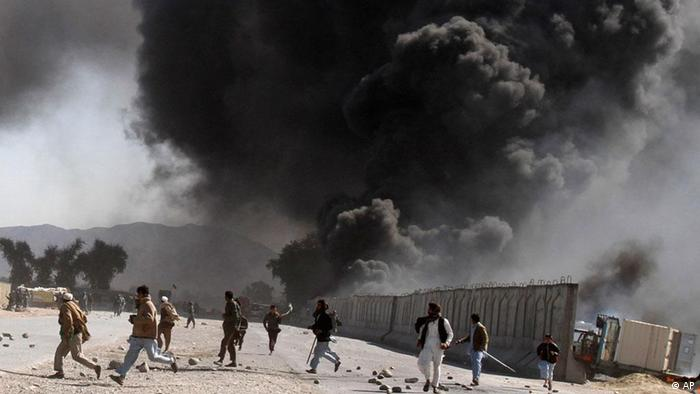 Protestors run as smoke raises from a burning truck during an anti-US demonstration at a NATO military base in Jalalabad, east of Kabul, Afghanistan, Wednesday, Feb. 22, 2012. Anti-American demonstrations continued for a second day Wednesday in Afghanistan over what the U.S. has said was the inadvertent burning of Muslim holy books at a NATO military base. (Foto:Rahmat Gul/AP/dapd)