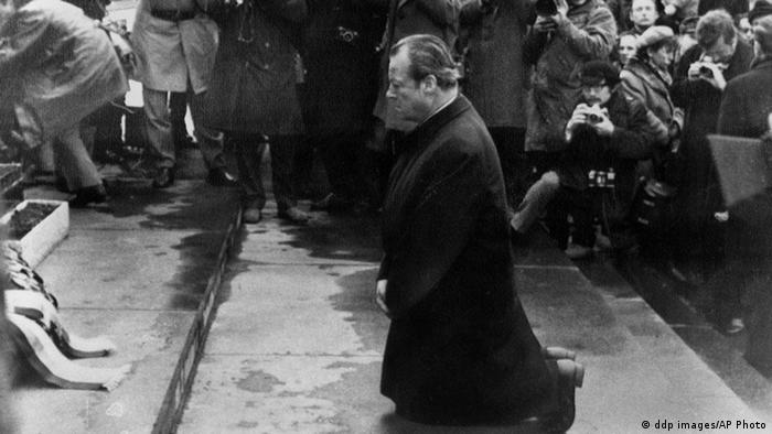 German Chancellor Willy Brandt, wearing a long dark coat, kneels on the steps of the Jewish Heroes' monument in Warsaw in a black-and-white photgraph (Photo: ddp images/AP Photo)