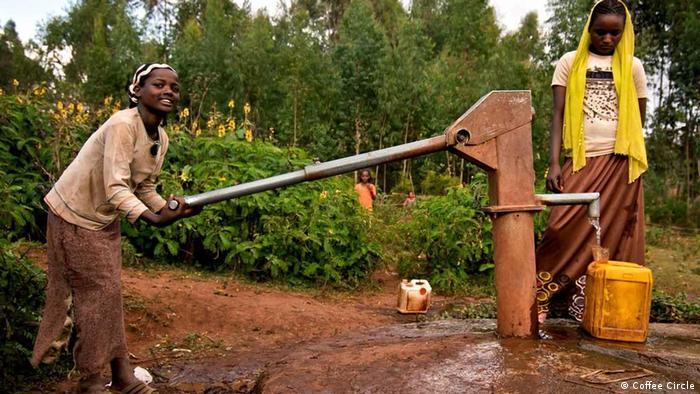 Zwei äthiopische Frauen an einem Brunnen. Die Frau links betätigt mit der Hand die Pumpe