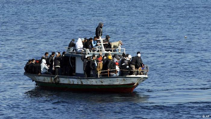 A boatload of would-be migrants believed to be from North Africa is seen moments before being rescued by the Italian Coast Guard in the waters off the Sicilian island of Lampedusa